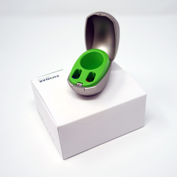 Phonak mini charger sat ontop of box on white background