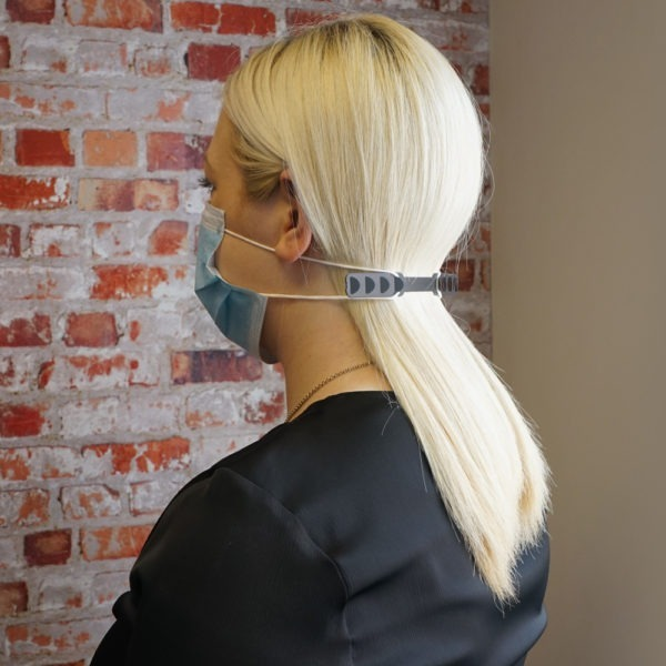 Woman with facemask and ear protector standing infront of brick background