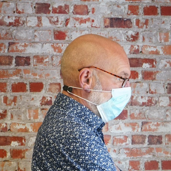 Man with facemask and ear protector standing infront of brick background