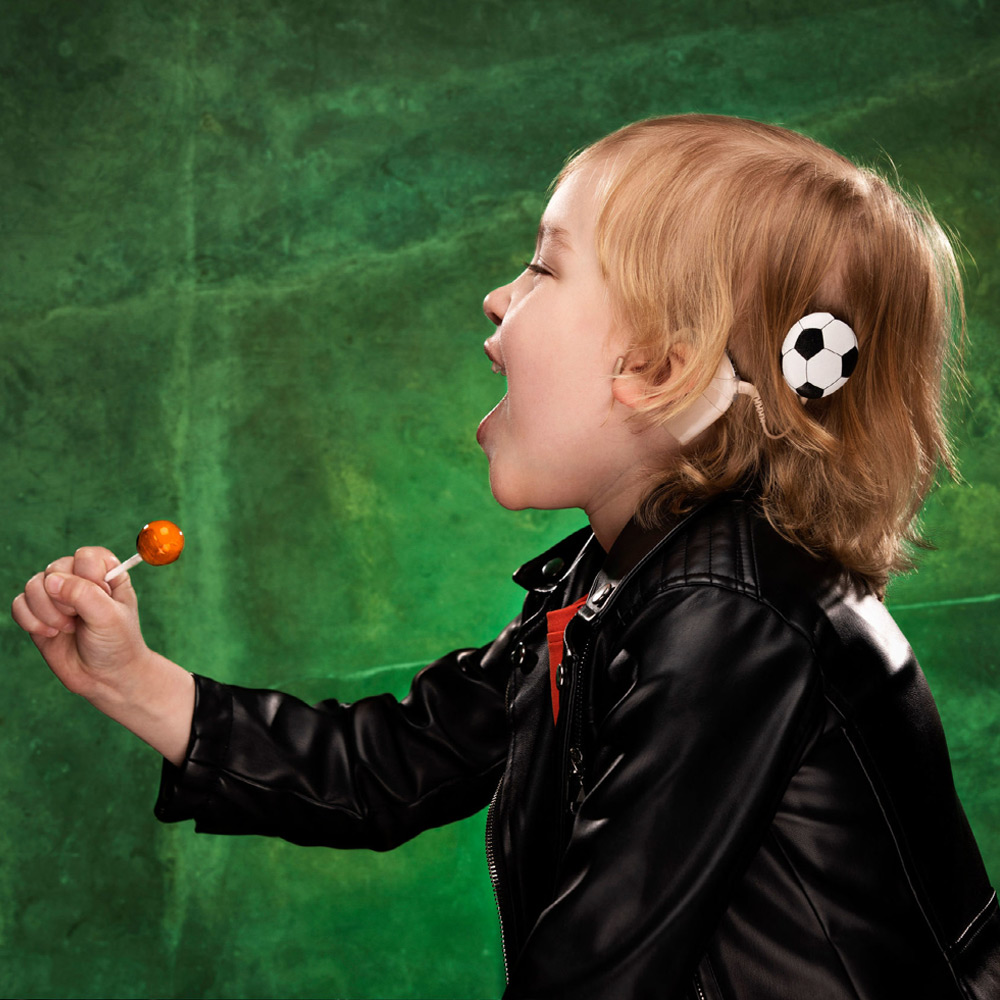 Child wearing Football hearing aid accessory from DeafMetal